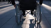 Back view of a disabled handicapped man in wheelchair, front of modern glass building for business deals.