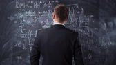 básico : Back middle shot of male against chalk board with mathematics formula equations. He thinking about solutions and try to understand high university task. Vídeos