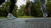 spor ayakkabısı : Runners couple male and female legs on pathway in autumn park asphalt road. Super slow motion rapidly shot from ground. Stok Video
