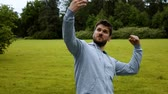 ginasta : Young sportsman jogger runner athlete makes selfie on his mobile phone in park in slow motion.