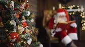 Blurred Santa Claus on xmas eve sitting in armchair hold old red silk album near focused in green christmas tree with toys and lights. Stock Footage