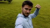 снимок : Male runner jogging in park. Fit male sport fitness training. Making selfie on his smartphone.