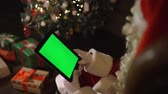 Santa Claus Choose Gifts on tabletPC. Tablet with Green Screen in Vertical Mode. Easy for tracking and keying. Near Xmas tree. Sliding movement fingers.