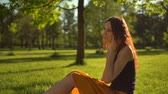 good time : Happy attractive sexy lady sitting on green grass in City Park and enjoying friendly conversation via digital phone. Stock Footage