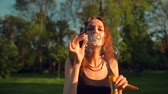 varinha : Attractive Handsome Woman Enjoying Nature. Standing in summer park. Young pretty female making soap bubbles. Super slow motion Close-up.