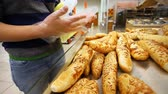 farinha integral : buyer chooses fresh bread in a supermarket