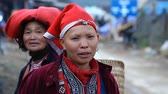 místní : Sapa, Vietnam - November 30, 2016 : A woman from the ethnic group of red Dao in a national costume . Posing in front of tourists and selling souvenirs is one of the main sources of income for Hmong