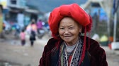 menšina : Sapa, Vietnam - November 30, 2016 : A woman from the ethnic group of red Dao in a national costume . Posing in front of tourists and selling souvenirs is one of the main sources of income for Hmong