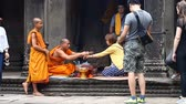 кхмерский : Siam Reap Angkor Wat, Cambodia - January 12, 2017:Cambodian buddhist monk reading mantra for tourist.Tourists and pilgrims leave donations for the preservation and restoration of complex Angkor Wat