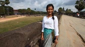 kamboçyalı : Siam Reap, Cambodia - January 12, 2017: Young Cambodian girl in traditional clothes on the background of the main entrance of Angkor Wat. Stok Video
