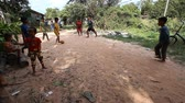 kamboçyalı : Siam Reap, Cambodia - January 13, 2017: Cambodian children play football on the road in their poor village . Living in poor settlements and slums in Cambodia