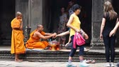 mnich : Siam Reap Angkor Wat, Cambodia - January 12, 2017:Cambodian buddhist monk reading mantra for tourist.Tourists and pilgrims leave donations for the preservation and restoration of complex Angkor Wat