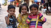 scarcity : Siam Reap, Cambodia - January 14, 2017: Three cheerful Cambodian children living in a poor Cambodian village.