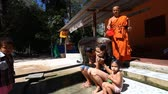 mnich : Siam Rip, Cambodia - January 15, 2017: Buddhist monk wire ritual cleansing cold water for a young family