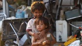 cambojano : Siam Reap, Cambodia - January 14, 2017: A homeless boy with his young sister living in a house from empty boxes and construction debris.