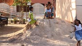 reap : Siam Reap, Cambodia - January 14, 2017: Children living in a poor village ride on cartons and plastic bags with a clay slide. Heavy childhood of children living in slums and poor villages of Cambodia Stock Footage