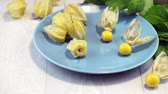 chinese gooseberry : Physalis fruits on blue ceramic plate and a wooden table.
