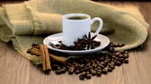food and drink : Coffee cup with burlap sack of roasted beans on rustic table
