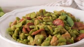 laurel leaves : Boiled broad bean with chorizo and laurel leaves on a white ceramic plate. Typical portuguese food.