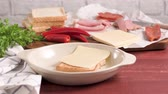 жарить : Ingredientes preparations of traditional Portuguese snack food. Francesinha sandwich of bread, cheese, pork, ham, sausages. On table. Стоковые видеозаписи