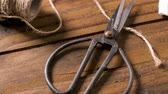 шпуля : Old-fashioned scissors cutting piece of garden twine on brown wooden  background.