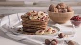 panqueca : Healthy breakfast table,  homemade pancakes with banana, goji and walnuts.