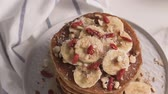 стек : Healthy breakfast table,  homemade pancakes with banana, goji and walnuts.