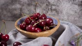 mesa de madeira : Red fresh cherries in bowls and a bunch of cherries on the table. Stock Footage