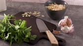 countertop : Fresh garden herbs on kitchen countertop. Parsley, garlic, knife and almons. The concept of food, healthy food. Stock Footage