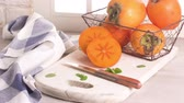 eat : Delicious fresh persimmon fruit on kitchen countertop. Stock Footage