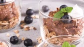 davranır : Glass cups of chocolate and chestnuts mousse with roasted almonds and oats decorated with black berries and mint leaves. Stok Video