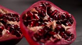 yarıya : Ripe pomegranate fruit and pomegranate seeds on dark background, close-up. Healthy vegetarian antioxidant organic diet food