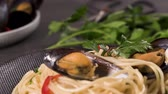 spaghetti allo scoglio : Homemade pasta spaghetti with mussels , peppers and parsley on rustic background. sea food meal. Filmati Stock