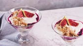 natural yogurt : Figs pudding parfait with yogurt, blueberry jam, figs, hazelnut, and cookies in glass on white marble background. Flatlay top view. Stock Footage