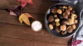 pép : Roasted chestnuts in cast iron pan over rustic wooden board and grey wooden background, selective focus. Stock mozgókép