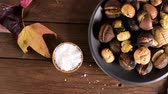 abriu : Roasted chestnuts in cast iron pan over rustic wooden board and grey wooden background, selective focus. Vídeos