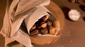 vegetarianismo : Roasted chestnuts in a paper cone, on a rustic kitchen countertop.