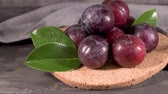 vitaminok : Delicious red plums in a cork plate on kitchen countertop. Stock mozgókép