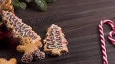 buzlu : Christmas holiday background with gingerbread cookies, candy canes and evergreens over wooden table. Christmas and New year food. Christmas decoration and sweets on wood background.