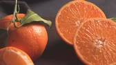 Fresh mandarin oranges or tangerines with leaves on textured dark background Dostupné videozáznamy