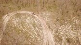 Aerial drone shot view of one enduro motorcycle drive through path or sandy trail on pine trees field during off road training in countryside. Adrenaline rush fun. Vídeos