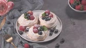 verão : Small pavlova cakes with fresh raspberries and blueberries. Stock Footage