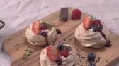 meringa : Small pavlova cakes with fresh raspberries and blueberries. Filmati Stock