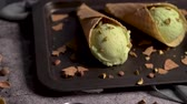 박하 : Balls of pistachio ice cream in waffle cones on a dark background.