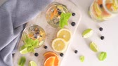 мохито : Summer healthy cocktails of citrus infused waters, lemonades or mojitos, with lime lemon orange blueberries and mint, diet detox beverages, in glasses on light background.