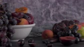 виноград : Fruits Still life with fruit on white ceramic bowl. Concrete wall. Dramatic light. Grapes, apricots and plums. Стоковые видеозаписи