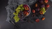 stilleven : Fruits Still life with fruit on white ceramic bowl. Concrete wall. Dramatic light. Grapes, apricots and plums. Stockvideo
