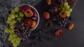 stilleben : Fruits Still life with fruit on white ceramic bowl. Concrete wall. Dramatic light. Grapes, apricots and plums. Videos