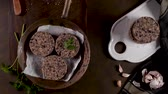 betterave : Raw veggie burger with black beans with parsley leaves on wood countertop. Vidéos Libres De Droits