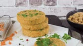 reçete : Raw veggie burger with chickpeas, vegetables and parsley leaves on kitchen countertop. Stok Video